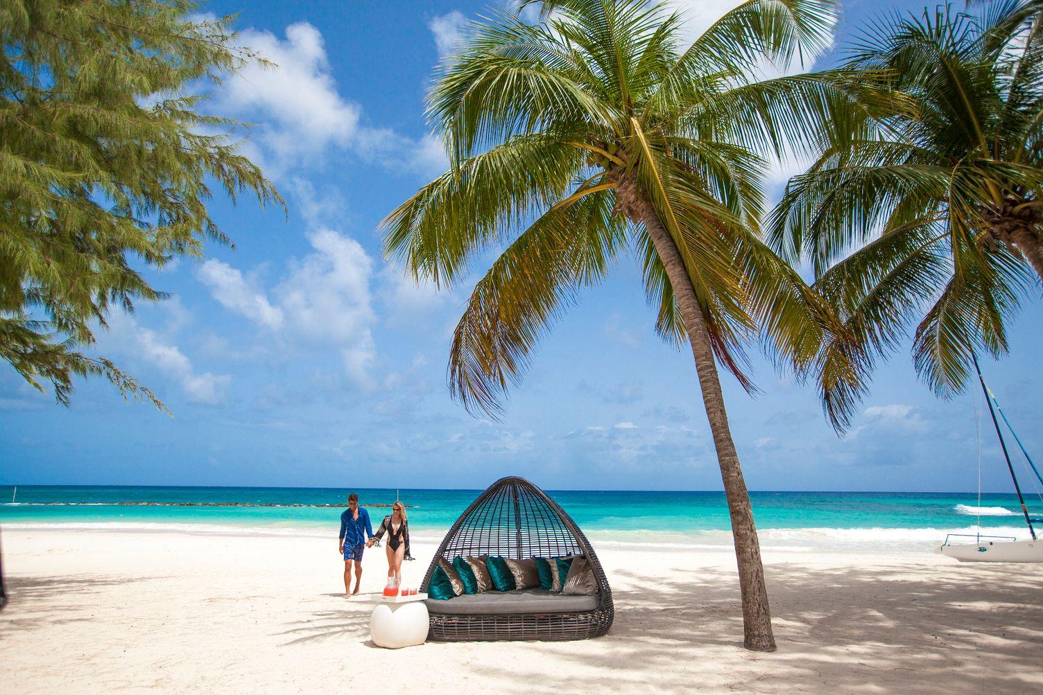 Paar läuft vom Wasser aus über den Strand. Rechts stehen Palmen.