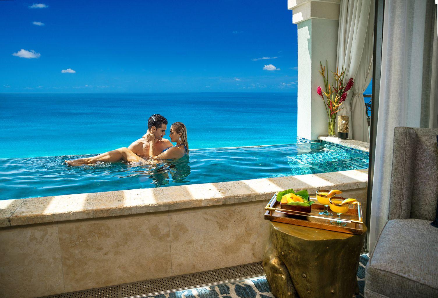 Paar in Infinity-Pool auf dem Balkon. Im Vordergrund ein Tablett mit Cocktails.