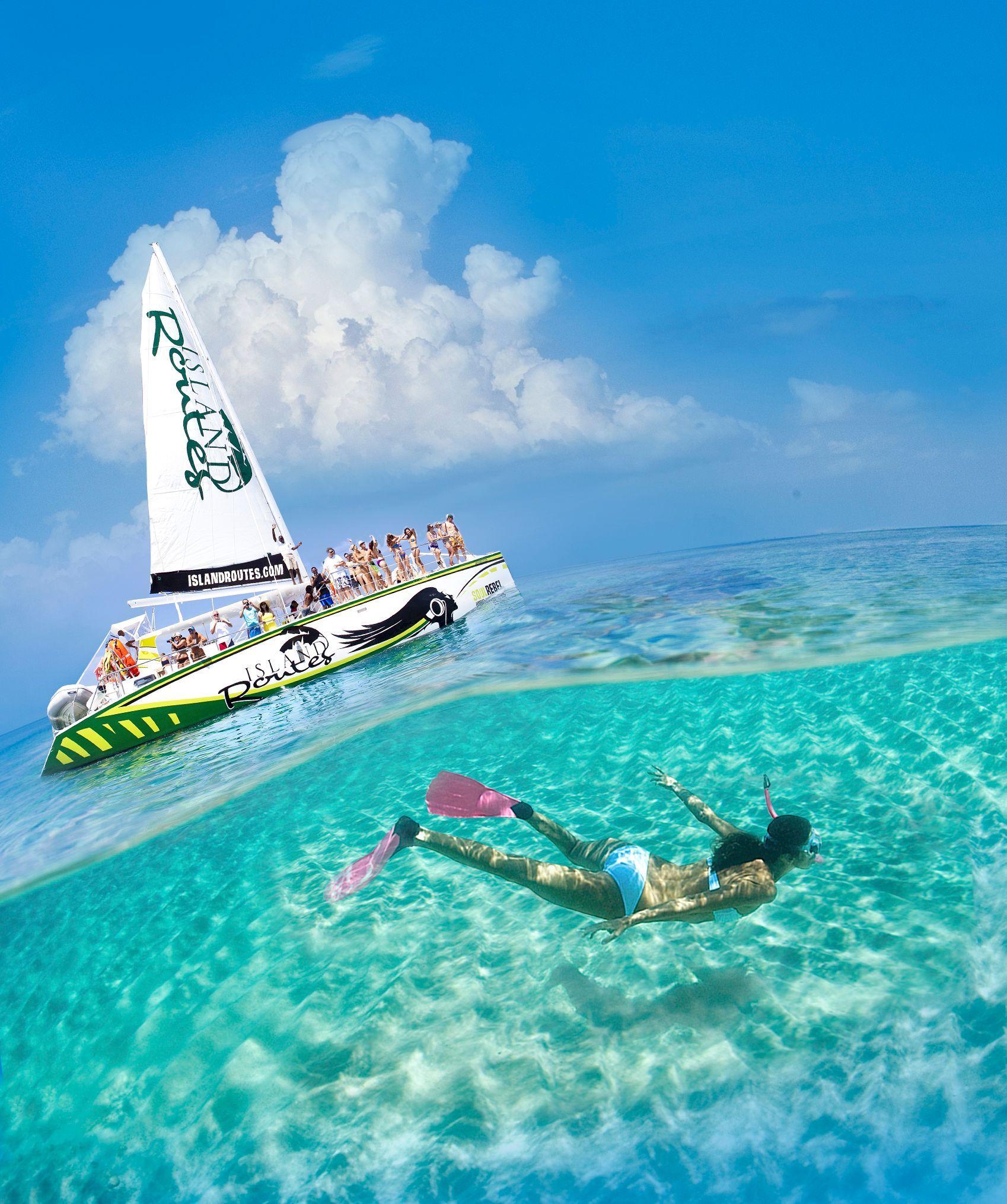 Schnorchler Unterwasser. Island Routes Katamaran mit Gästen im Hintergrund.