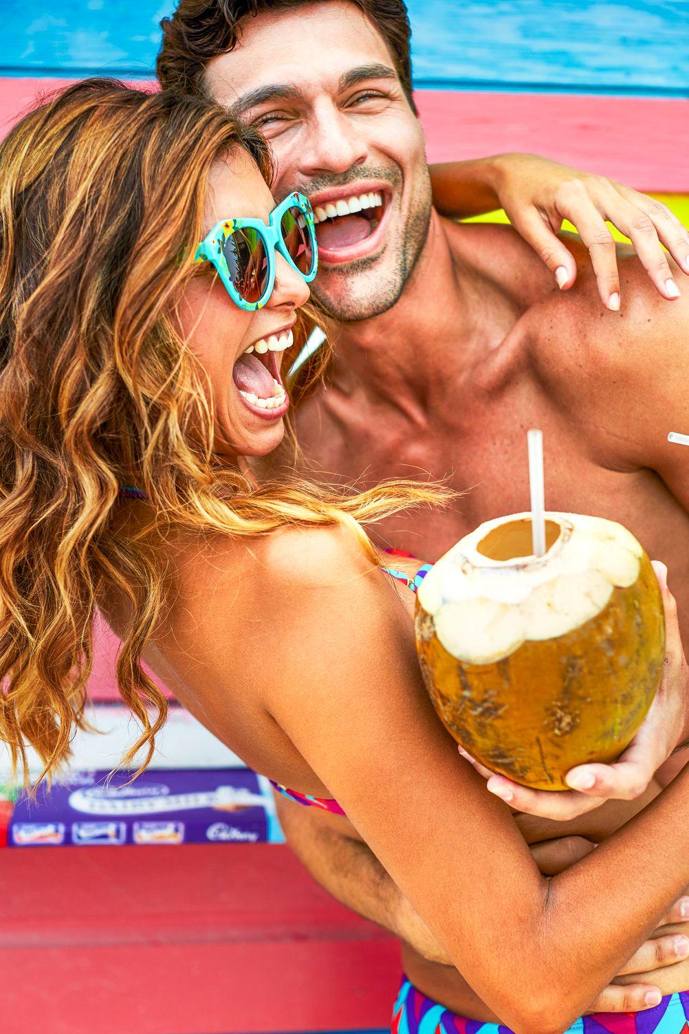 Man hält Frau in einem Arm, im anderen eine Kokosnuss mit Strohhalm. Sie lachen. Im Hintergrund ist ein buntes Hus