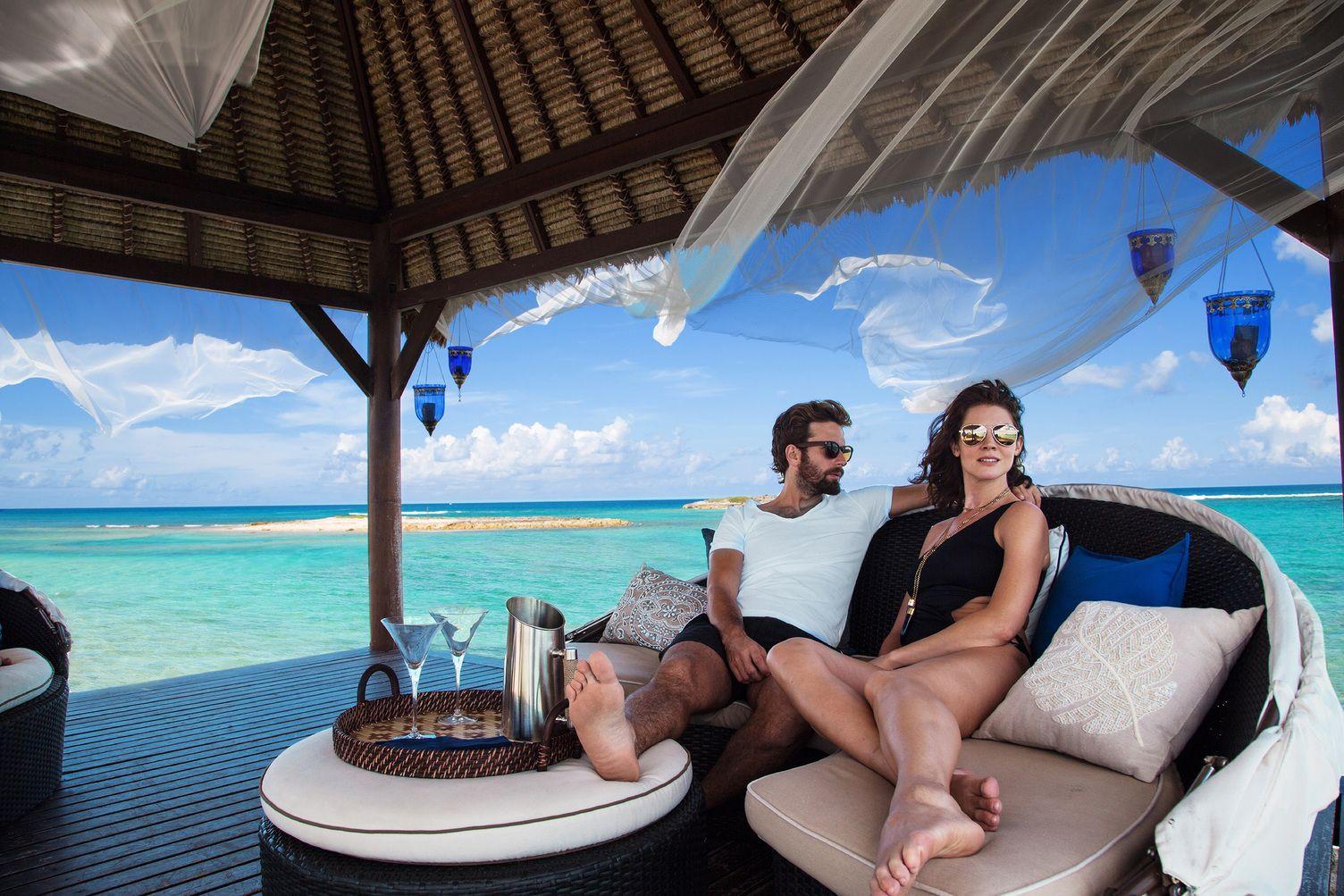 Paar sitzt in Strand-Kabana. Im Hintergrund das Meer.