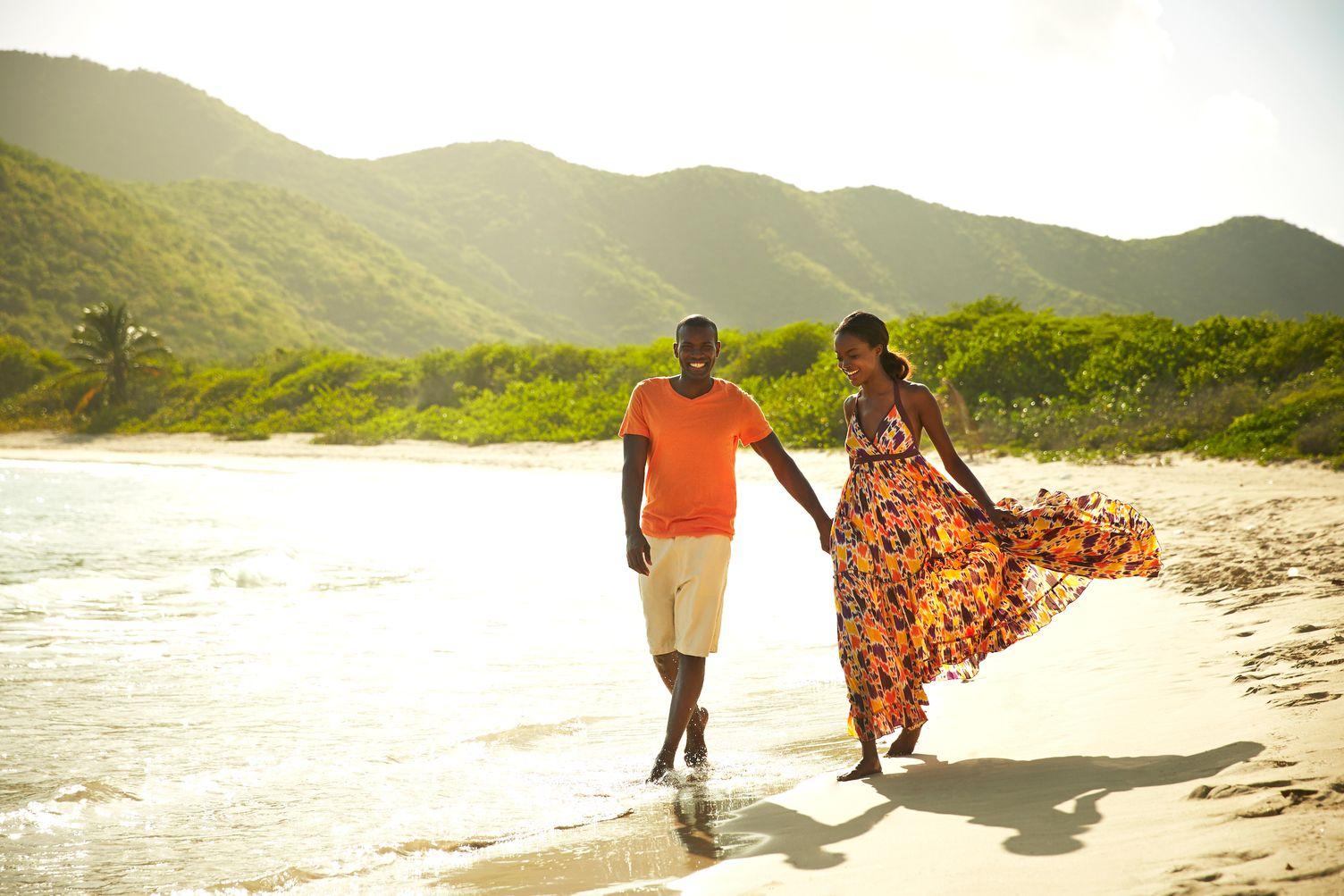 Paar spaziert Hand in Hand am Strand entlang. Im Hintergrund die bewachsenen Berge der Insel.
