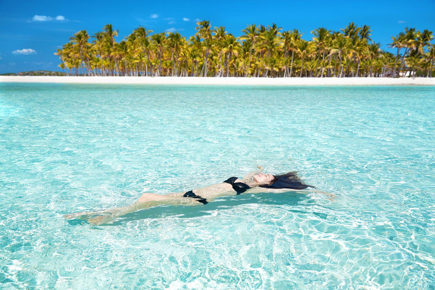Frau liegt im Wasser. Im Hintergrund ist ein leerer Strand mit Palmen. Das Wasser ist klar.