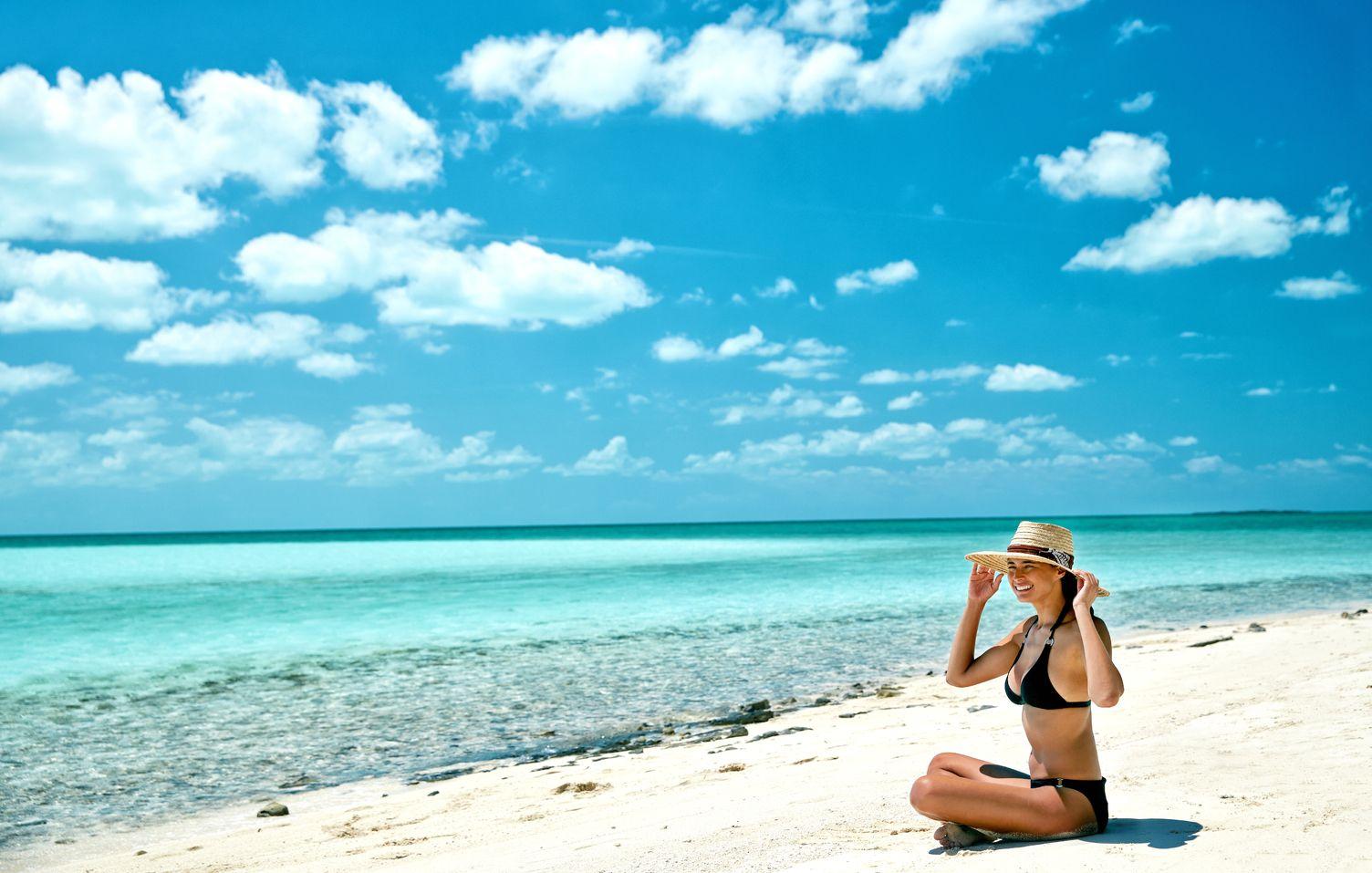 Frau sitzt am Strand mit Sonnenhut auf. Das Meer ist klar. Sie hält ihren Hut fest.