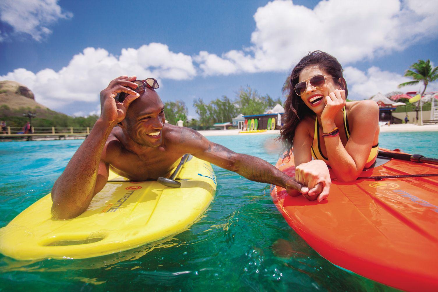 Paar im Wasser liegt auf Surfbrettern. Im Hintergrund der Strand und das Resort.