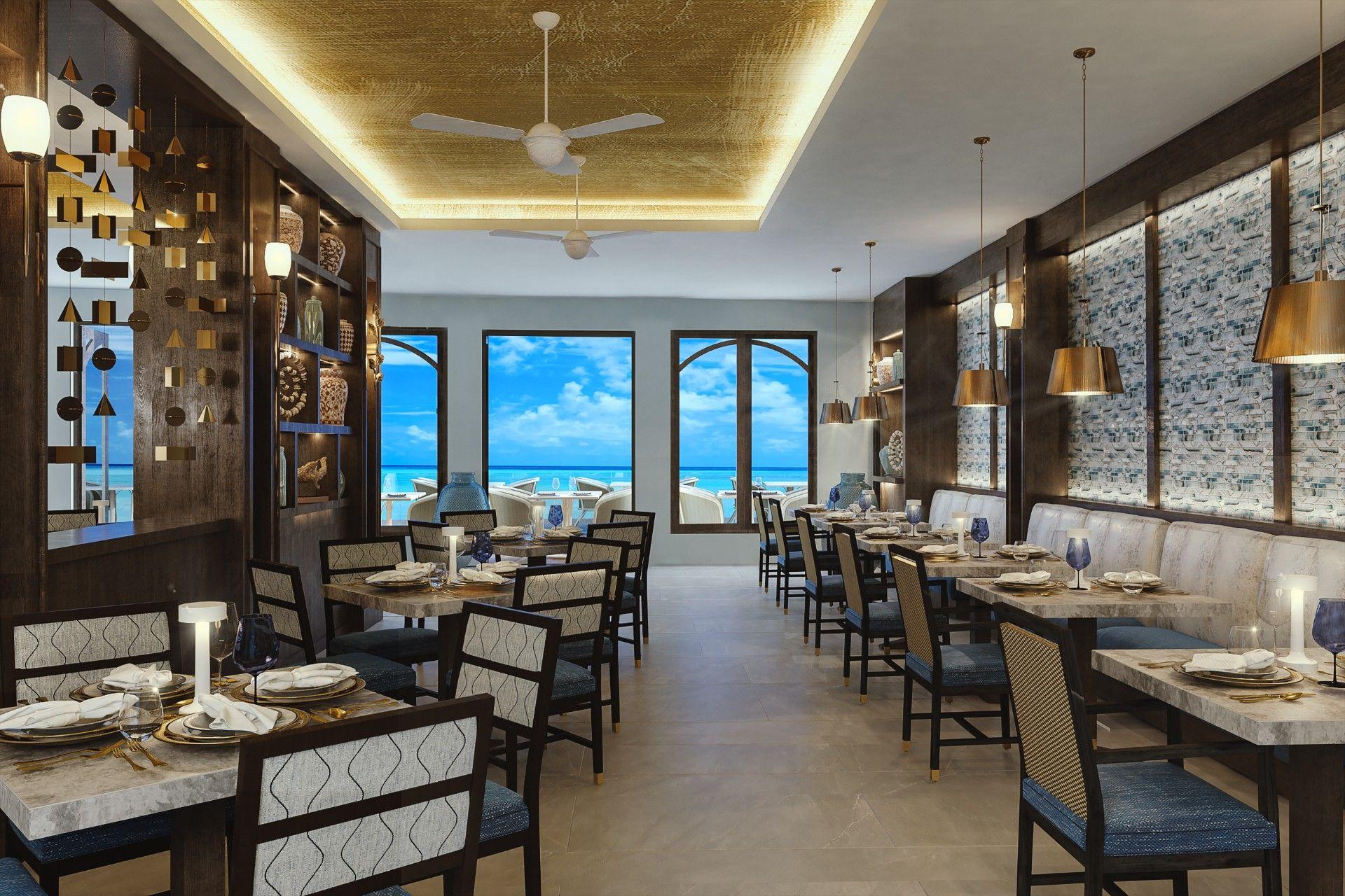 Restaurant von Innen. Modern eingerichtet. Durchs Fenster sieht man das Meer und einen Außensitzbereich.