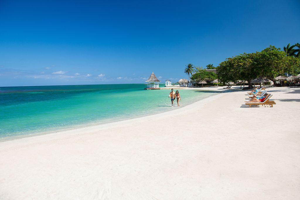 Paar spaziert am Strand an sonnenden Gästen vorbei. Strandpavillons im Hintergrund. Sonne scheint.