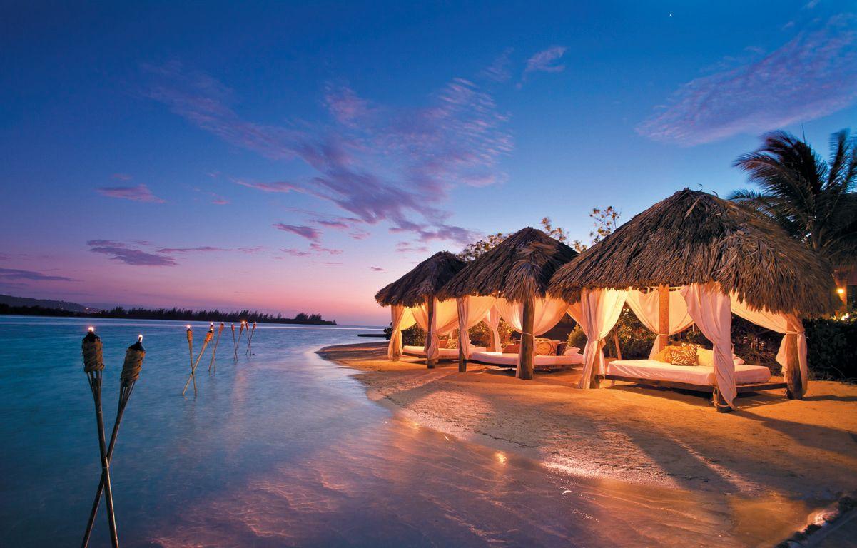 Beleuchtete Strand-Kabanas im Sonnenuntergang. Links sind Fackeln aufgestellt.
