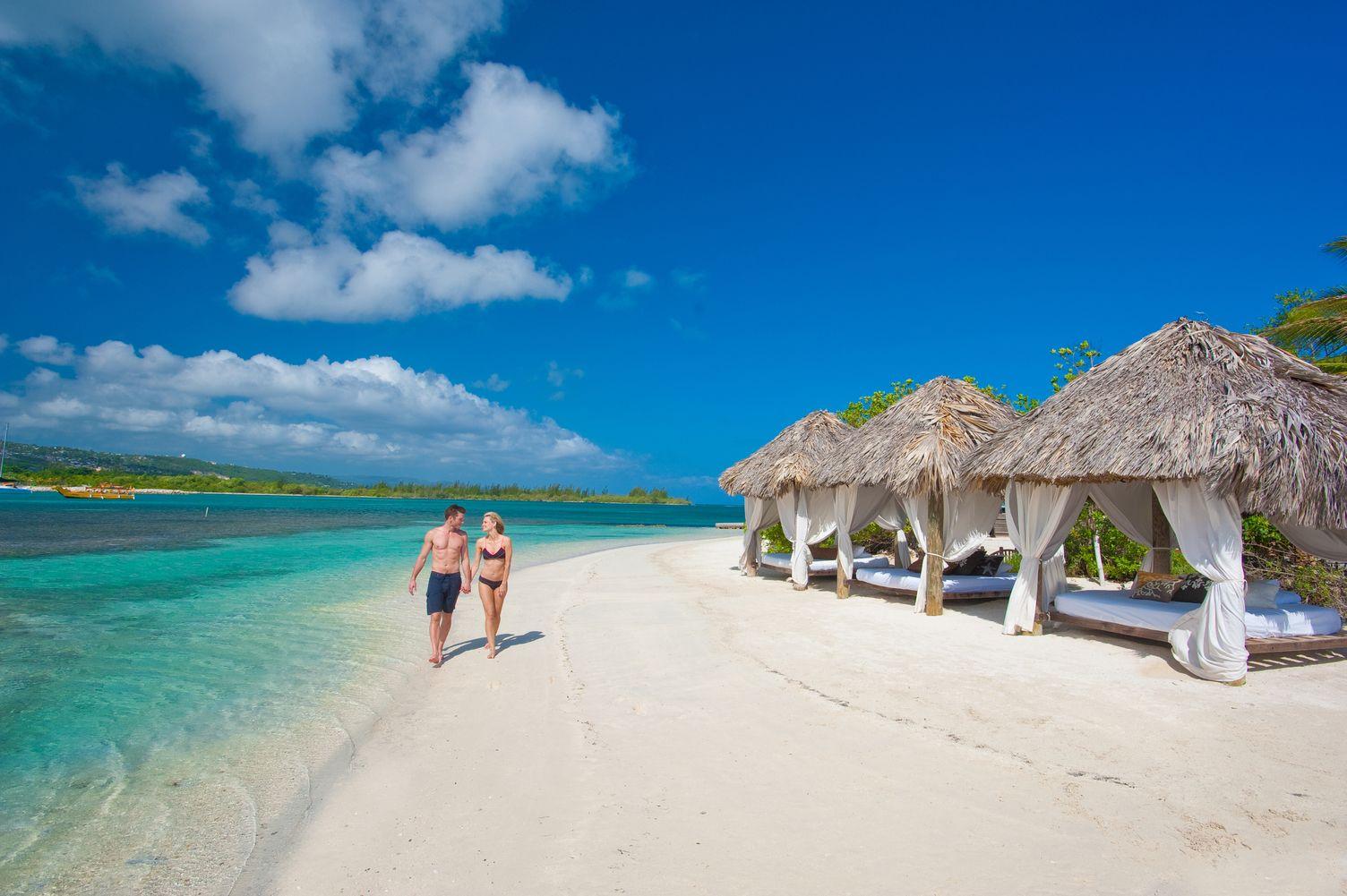 Paar spaziert am Strand entlang, Hand in Hand. Rechts stehen Strand Kabanas