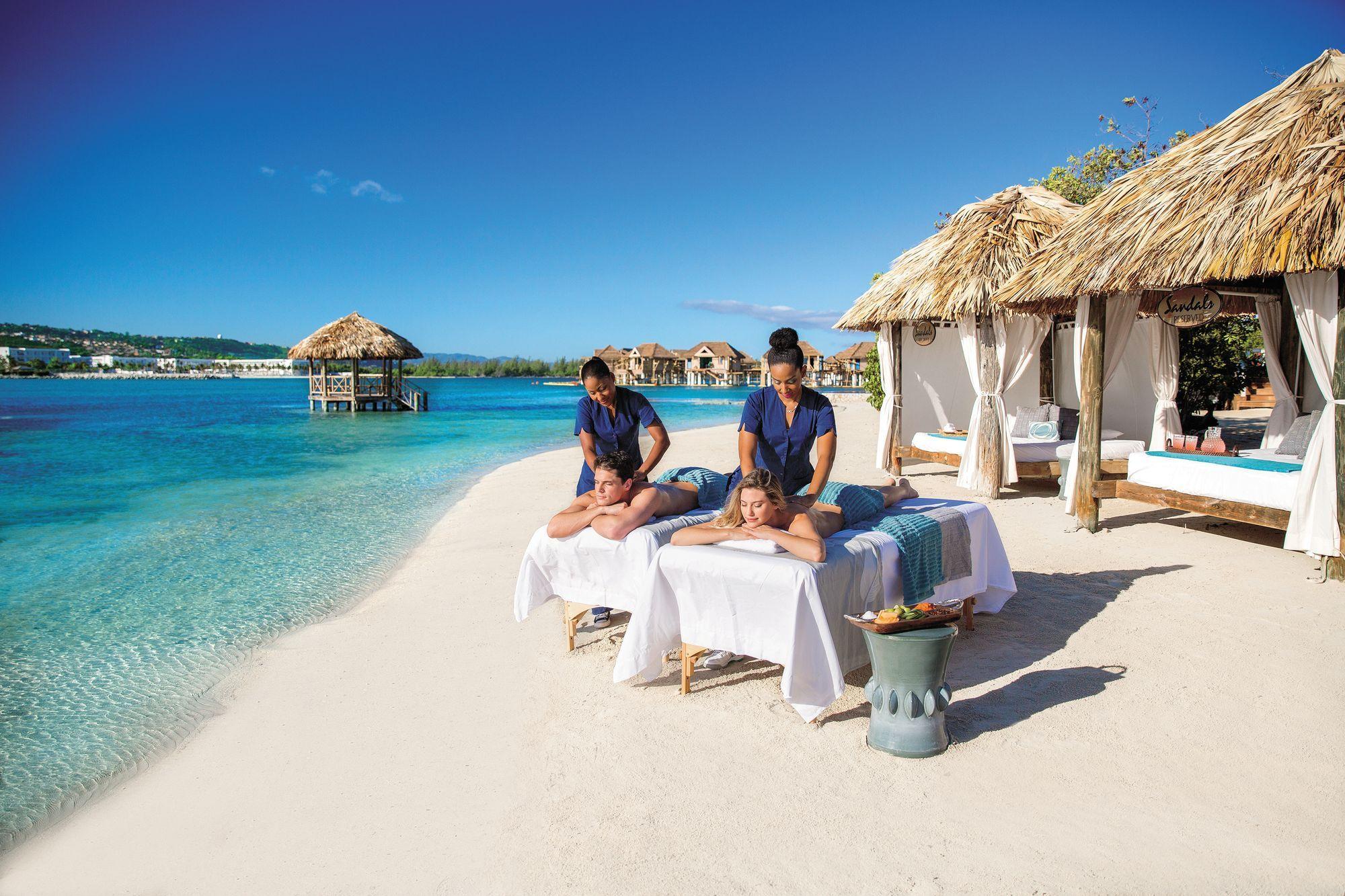 Paarmassage im Strand. Strandcabanas und Over-the-Water Suiten im Hintergrund.