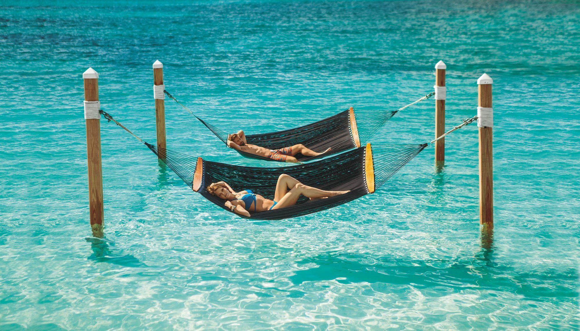 Paar liegt in Hängematten die über das Wasser gespannt sind. Frau sieht in die Kamera.